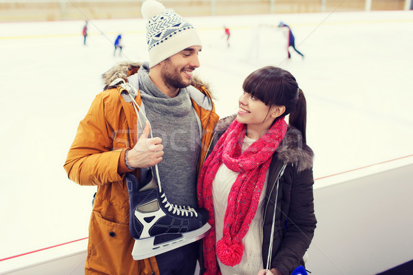 happy couple with ice-skates on skating rink Stock photo © dolgachov