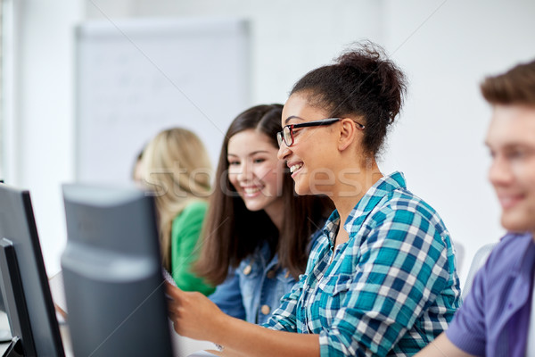 happy high school students in computer class Stock photo © dolgachov