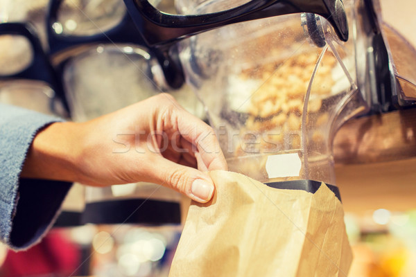 close up of hand pouring nuts to paper bag Stock photo © dolgachov