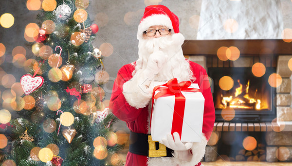 santa claus with gift making hush gesture at home Stock photo © dolgachov