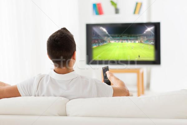 Homem assistindo jogo de futebol tv casa de volta Foto stock © dolgachov
