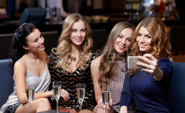 women with champagne taking selfie at night club Stock photo © dolgachov