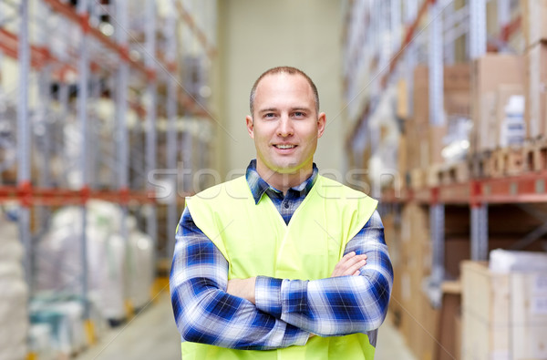 happy man in reflective safety vest at warehouse Stock photo © dolgachov