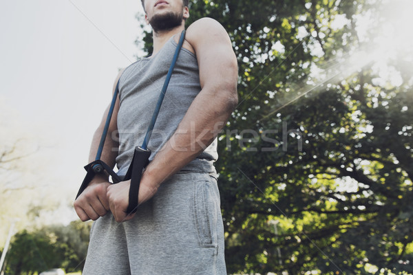 young man exercising with expander in summer park Stock photo © dolgachov