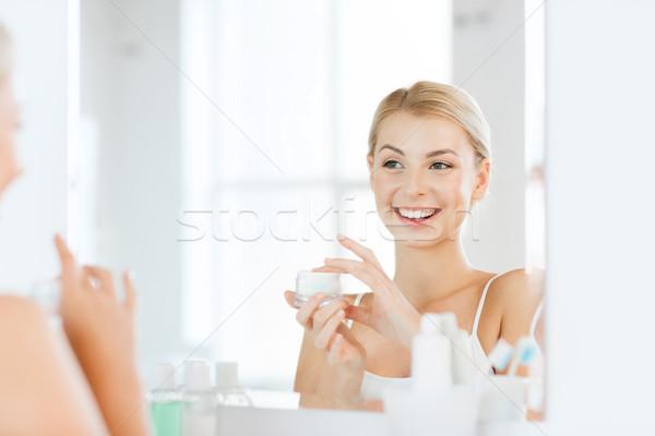 Heureux femme crème visage salle de bain Photo stock © dolgachov