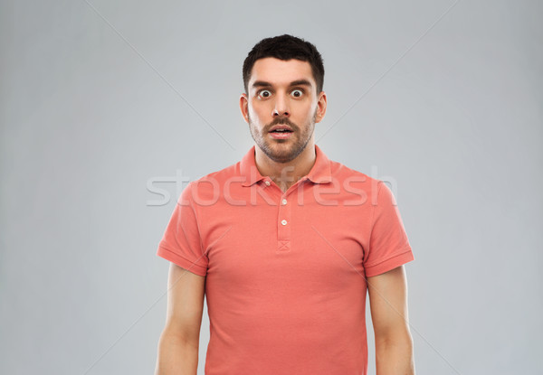 surprised man in polo t-shirt over gray background Stock photo © dolgachov