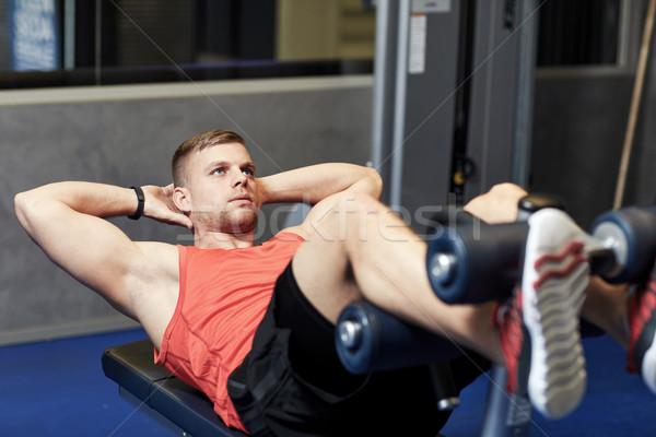 young man making abdominal exercises in gym Stock photo © dolgachov