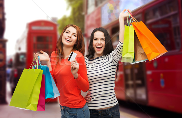 teenage girls with shopping bags and credit card Stock photo © dolgachov