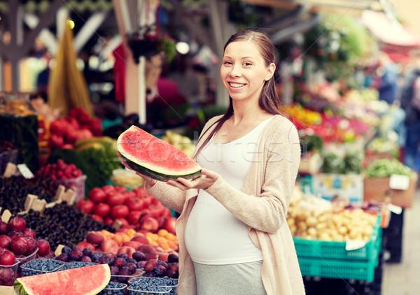 pregnant woman holding watermelon at street market Stock photo © dolgachov