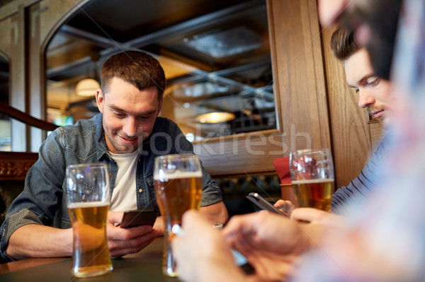 Mannen smartphones drinken bier bar pub Stockfoto © dolgachov