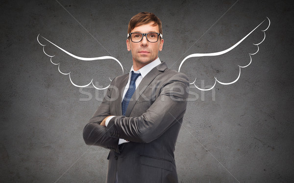 businessman with angel wings over gray Stock photo © dolgachov