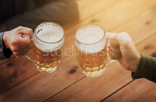 close up of hands with beer mugs at bar or pub Stock photo © dolgachov