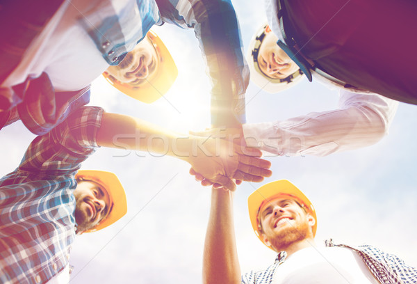 close up of builders in hardhats with hands on top Stock photo © dolgachov