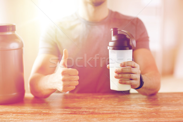 man with protein shake bottle showing thumbs up Stock photo © dolgachov