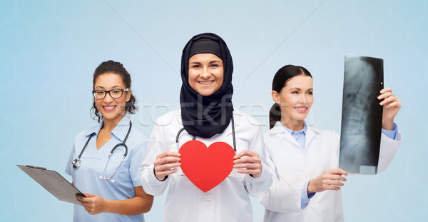 happy doctors with red heart, x-ray and clipboard Stock photo © dolgachov