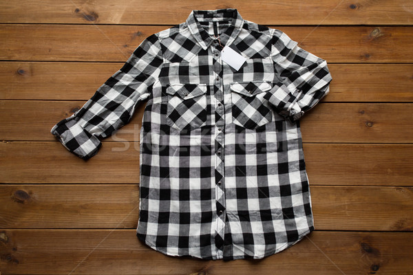 checkered shirt with tag on wooden background Stock photo © dolgachov