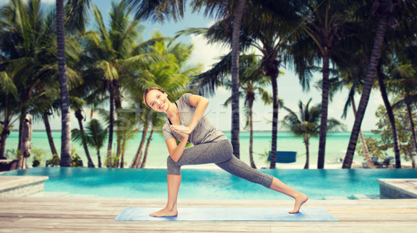 woman making yoga low angle lunge pose over beach Stock photo © dolgachov
