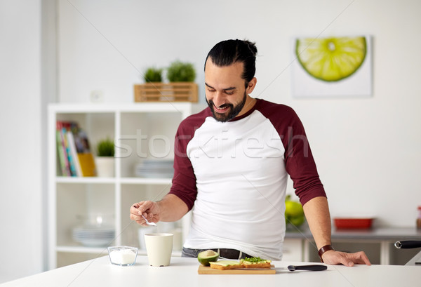 man adding sugar to cup for breakfast at home Stock photo © dolgachov