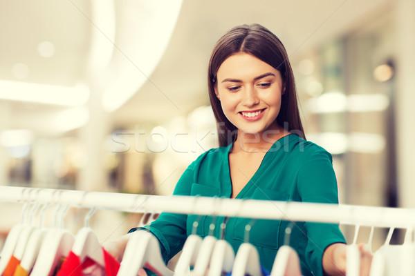 happy woman choosing clothes at shopping mall Stock photo © dolgachov