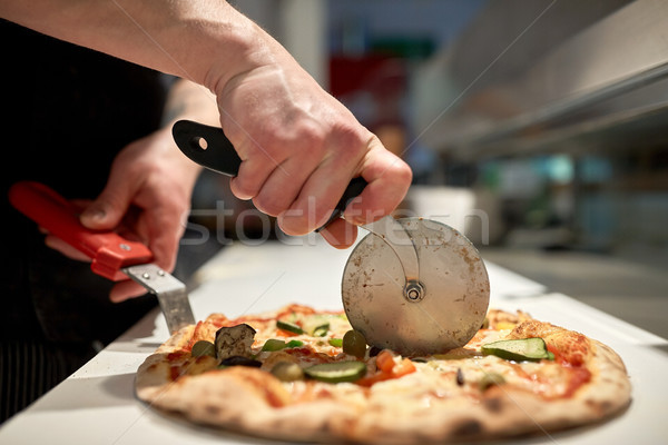 cook cutting pizza to pieces at pizzeria Stock photo © dolgachov