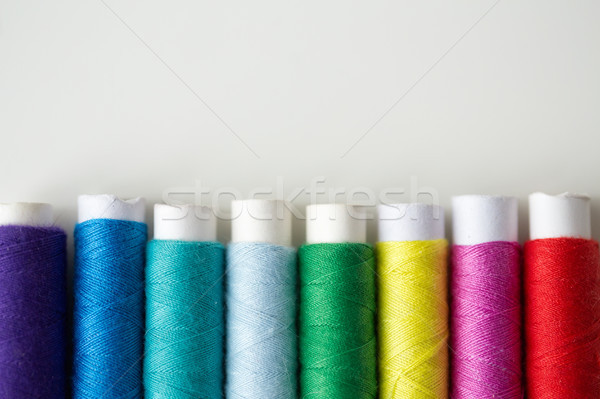 row of colorful thread spools on table Stock photo © dolgachov