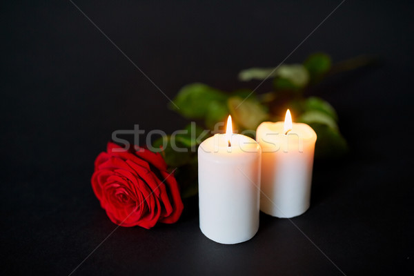 red rose and burning candles over black background Stock photo © dolgachov