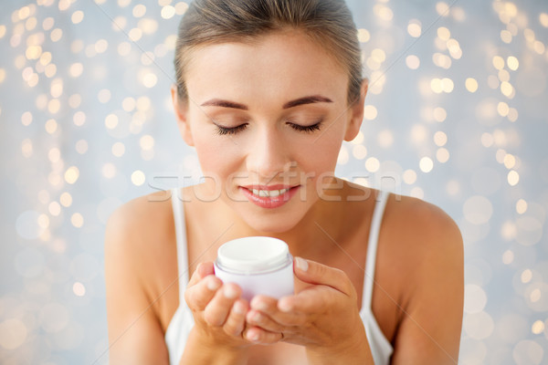 close up of happy woman holding and smelling cream Stock photo © dolgachov