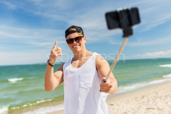 man with smartphone selfie stick on summer beach Stock photo © dolgachov