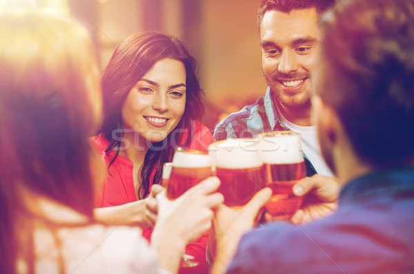 friends drinking beer and clinking glasses at pub Stock photo © dolgachov