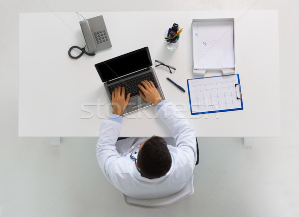 doctor with cardiogram and laptop at clinic Stock photo © dolgachov