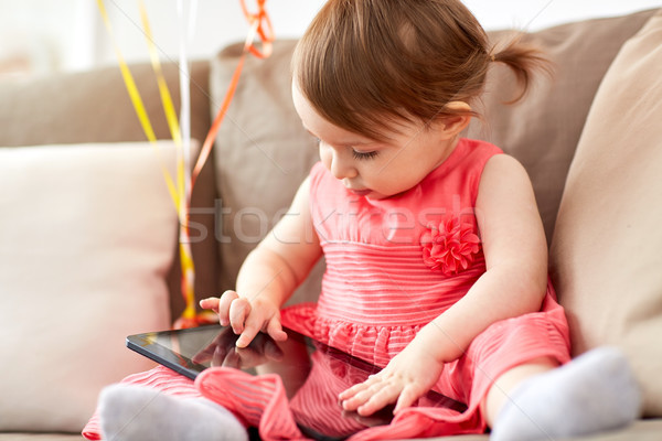 baby girl with tablet pc sitting on sofa at home Stock photo © dolgachov