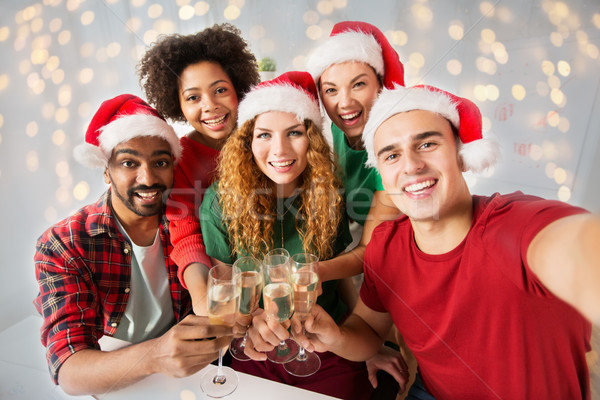 happy friends celebrating christmas at office party Stock photo © dolgachov