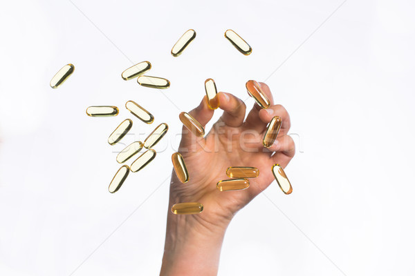 hand picking cod liver oil capsules up Stock photo © dolgachov