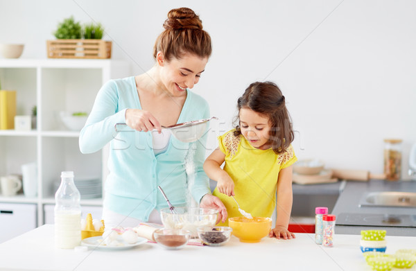 happy mother and daughter baking at home Stock photo © dolgachov