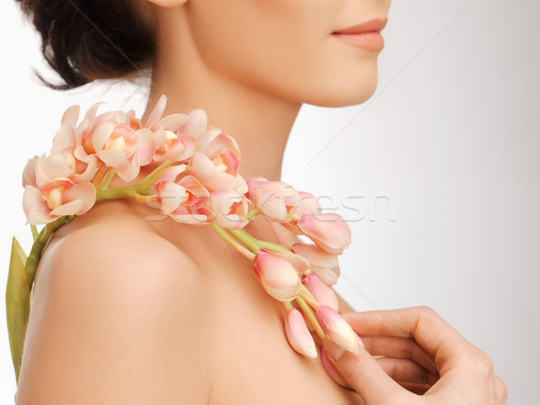 woman's shoulder and hands holding orchid flower Stock photo © dolgachov