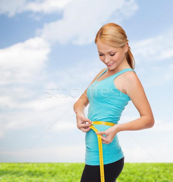 sporty woman with measuring tape Stock photo © dolgachov