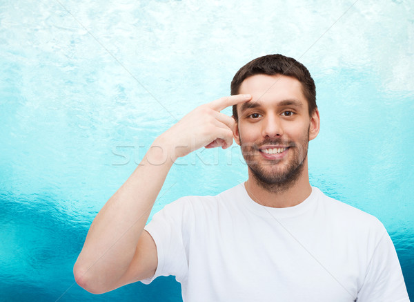 Glimlachend jonge knappe man wijzend voorhoofd gezondheid Stockfoto © dolgachov