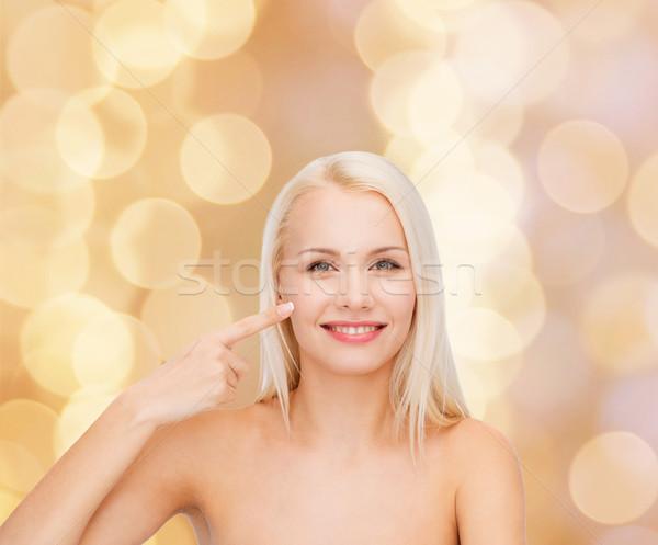Sorridente mulher jovem indicação bochecha saúde beleza Foto stock © dolgachov