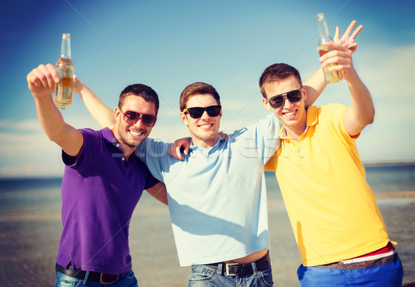 male friends on the beach with bottles of drink Stock photo © dolgachov