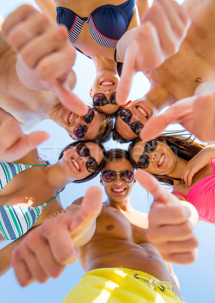 smiling friends showing thumbs up in circle Stock photo © dolgachov