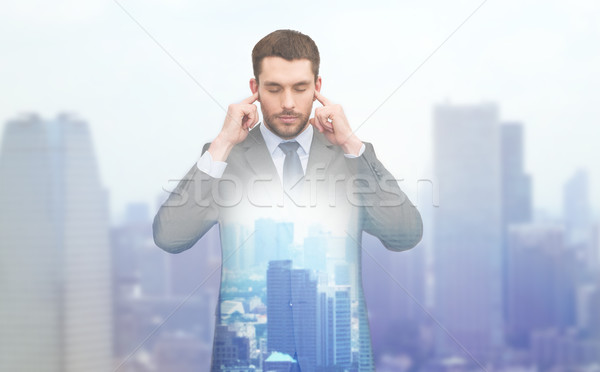 annoyed businessman covering ears with his hands Stock photo © dolgachov