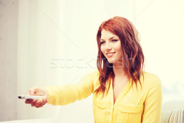 Gülen genç kadın kontrol ev televizyon Stok fotoğraf © dolgachov