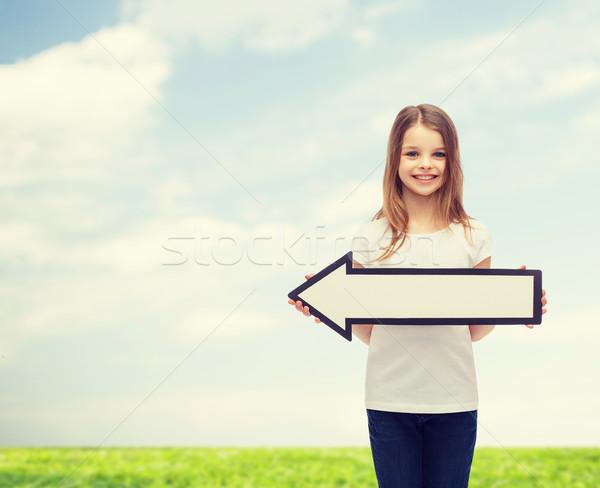 smiling girl with blank arrow pointing left Stock photo © dolgachov