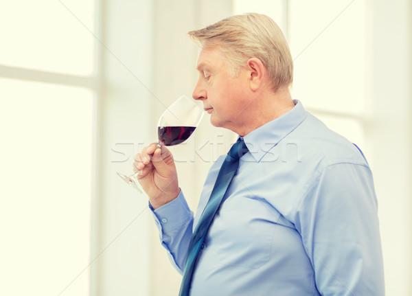 older man smelling red wine Stock photo © dolgachov
