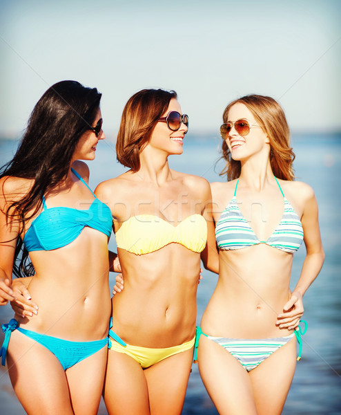 girls in bikinis walking on the beach Stock photo © dolgachov