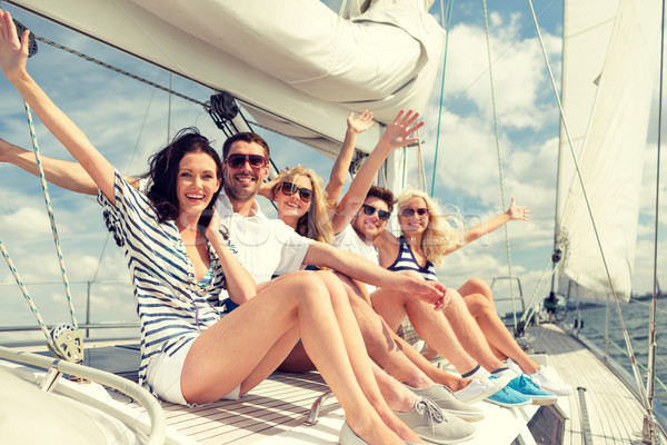 smiling friends sitting on yacht deck and greeting Stock photo © dolgachov