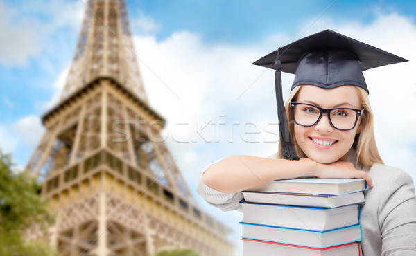 student in trencher with books over eiffel tower Stock photo © dolgachov