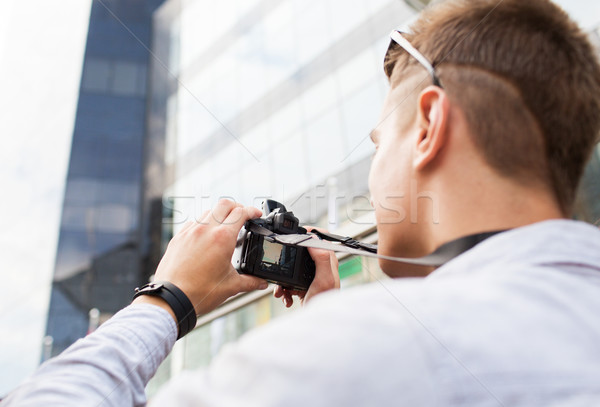 Stock photo: close up of young man with digital camera in city