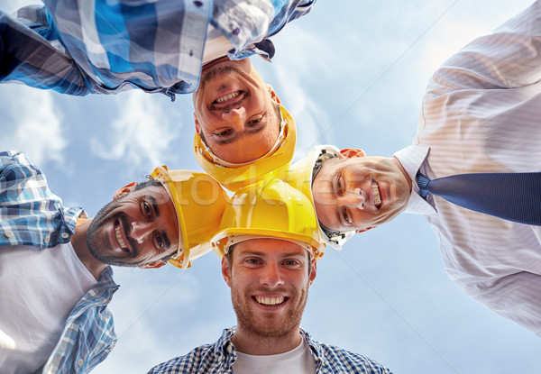 close up of builders wearing  hardhats in circle Stock photo © dolgachov