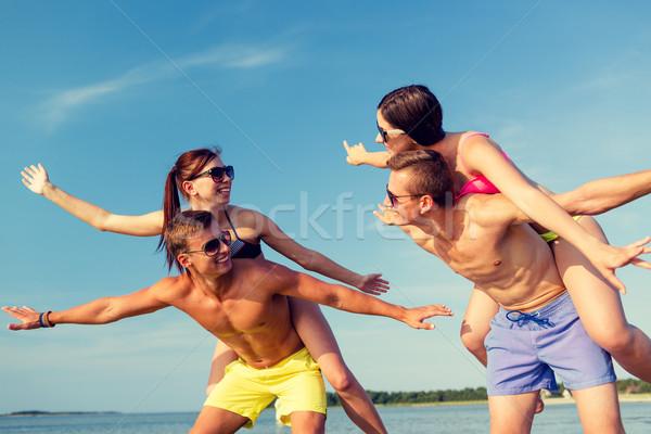 smiling friends having fun on summer beach Stock photo © dolgachov